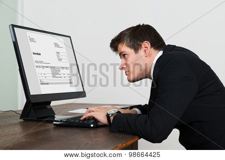 Businessman Looking At Invoice On Computer
