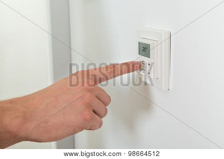 Person Hands Adjusting Temperature On A Digital Thermostat