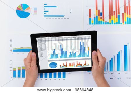 Person Analyzing Financial Graph On Digital Tablet