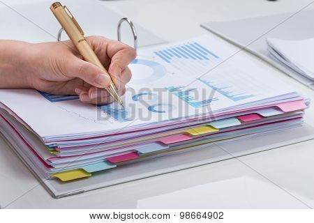 Person Analyzing Graphs At Desk