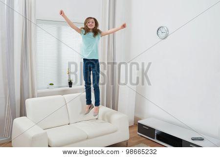 Girl Jumping On Sofa