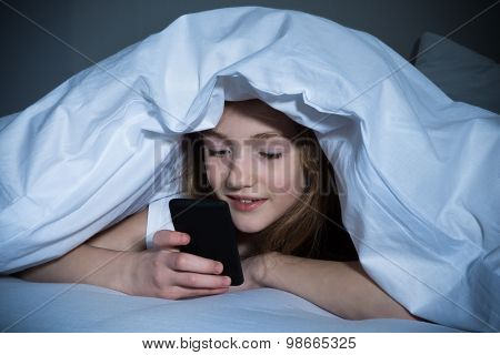 Girl With Mobile Phone Lying Under Blanket