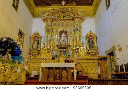 Heavily golden religious decorated alter inside San Diego church shot from front angle.