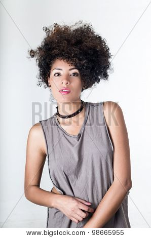 Hispanic brunette model with afro like hair wearing casual grey sleeveless shirt posing for camera w