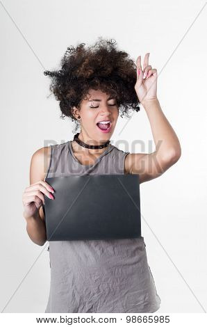Hispanic brunette rebel model with afro like hair wearing grey sleeveless shirt holding blank board