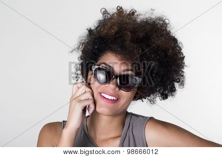 Headshot hispanic brunette rebel model with afro like hair wearing grey sleeveless shirt and sunglas