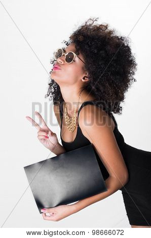 Hispanic model wearing black sexy dress and sunglasses holding blank board leaning forward making pe
