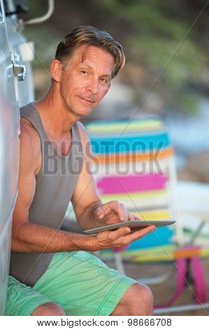 Man On Vacation With Tablet Computer