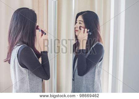 Asian Portrait Beautiful Woman Making Make-up With Brush On Face Near Mirror