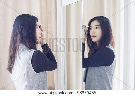 Asian Portrait Beautiful Woman Making Make-up With Brush On Eyebrow Near Mirror