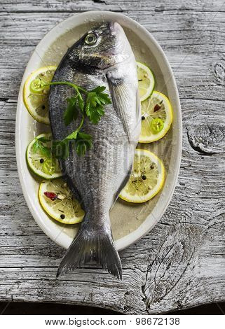 Fresh Dorado Fish On An Oval Platter With Lemon And Spices On A Light Wooden Surface