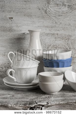 White Vintage Crockery - Ceramic Bowl, Vase, Porcelain Tea Cups On White Wooden Background