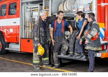 Team of smiling firefighters conversing by firetruck at station