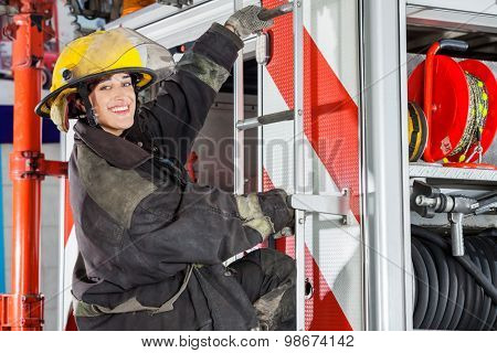 Side view portrait of smiling female firefighter standing on truck at fire station