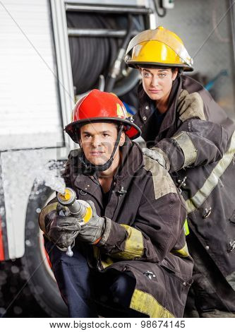 Confident male and female firefighters practicing at fire station