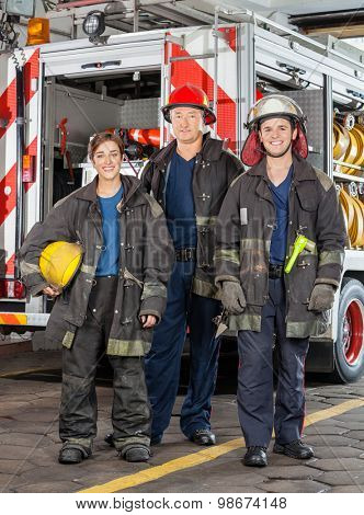 Full length portrait of confident firefighters standing against truck at fire station