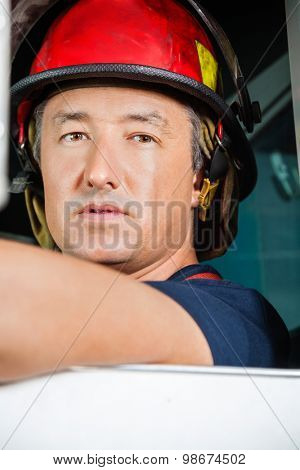 Closeup portrait of confident male firefighter sitting in firetruck