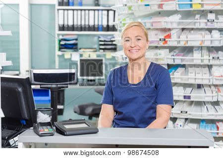 Portrait of confident assistant sitting at cash counter in pharmacy