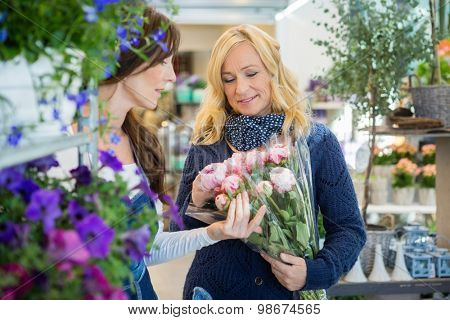 Sales woman showing flower bouquet to female customer at store