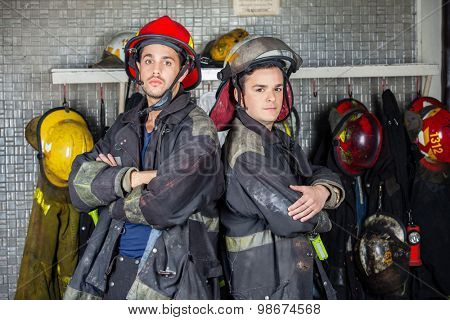 Portrait of confident firefighters standing arms crossed at fire station