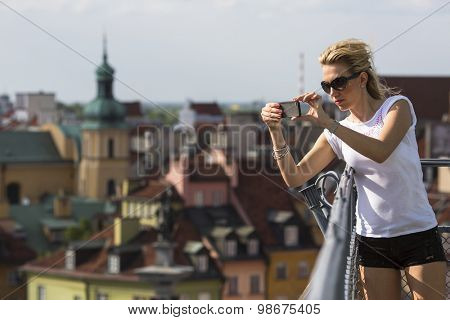 Young woman on the observation deck takes a picture of the old town on his mobile phone.