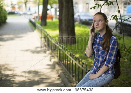 Teenage girl anxiously talking on the cell phone while sitting outdoors.