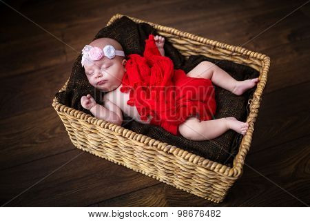 Newborn baby girl sleeping inside the wicker basket