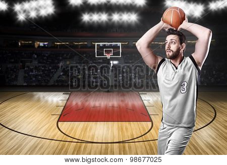 Basketball Player on a white uniform in basketball court