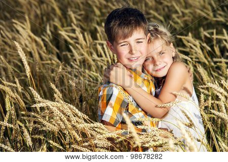 Happy children in the wheat field on a bright sunny day. Friendship. Summer holidays.