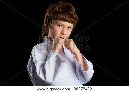 Karate boy in white kimono isolated on black background