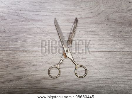 A pair of scissors sits half open on a worn butcher block counter top