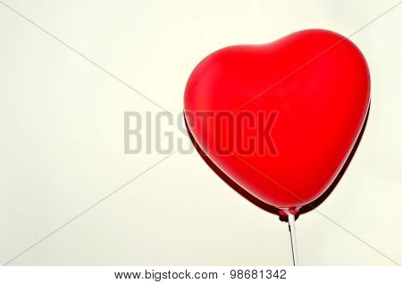 a heart-shaped balloon against a white background