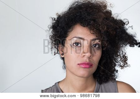 Headshot hispanic brunette model with messy makeup and hair looking unhappily into camera, white bac