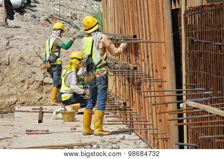 Construction workers fabricate retaining wall reinforcement bar and formwork at the construction sit