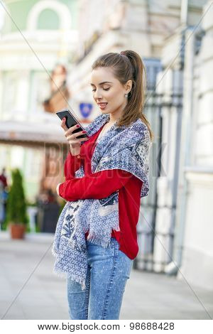 Beautiful casual woman texting on her cell phone on summer street city