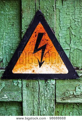 Old Rusty Warning High Voltage Sign On Cracked Wooden Surface