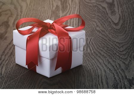 gift box with red bow on rustic table