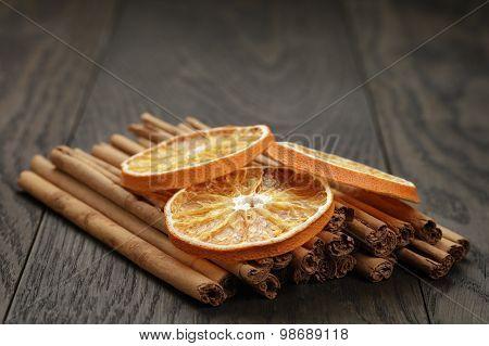 true cinnamon sticks and dried oranges, oak table