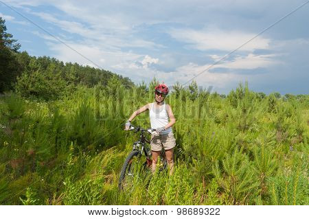 Active woman riding bicycle in forest, sport and oudoor fitness