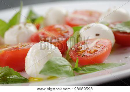caprese salad with mini mozzarella balls and tomatoes