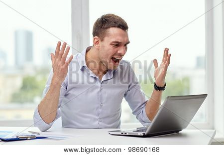 business, people, stress, fail and technology concept - angry businessman with laptop computer and papers shouting in office