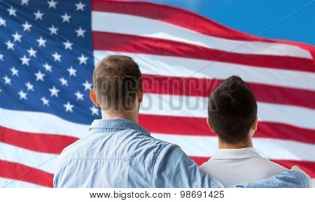 people, homosexuality, same-sex marriage, gay and love concept - close up of happy male gay couple or friends hugging from back over american flag background