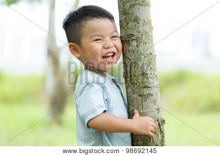 Excited Baby boy hold with tree bark