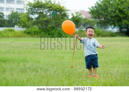 Excited Baby boy hold with orange balloon