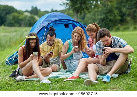 travel, tourism, hike, technology and people concept - group of friends with smartphone and tent at camping