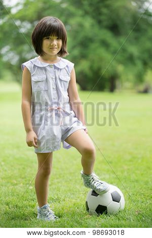 Little Asian Girl Playing Football At The Park