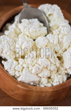 curd in brown wooden bowl closeup
