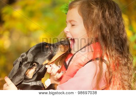 Child And Dog Embracing And Kissing.