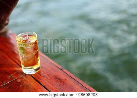 A Glass of alcohol with ice beside river