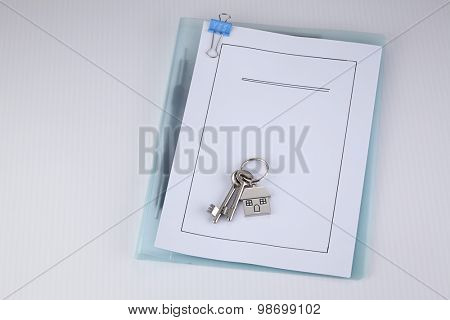 House shaped key chain with keys on top of loan application